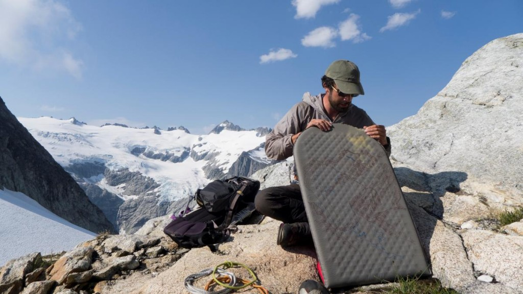NOLS participant sits on rocky outcrop holding inflatable sleeping pad with snowy mountains behind