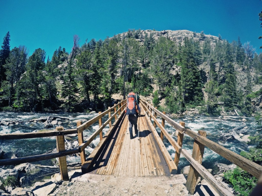 Backpackers cross a bridge over a river