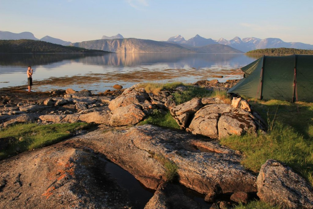 boy stands on a rocky shoreline with mountains reflected in glassy water and a green tent nearby