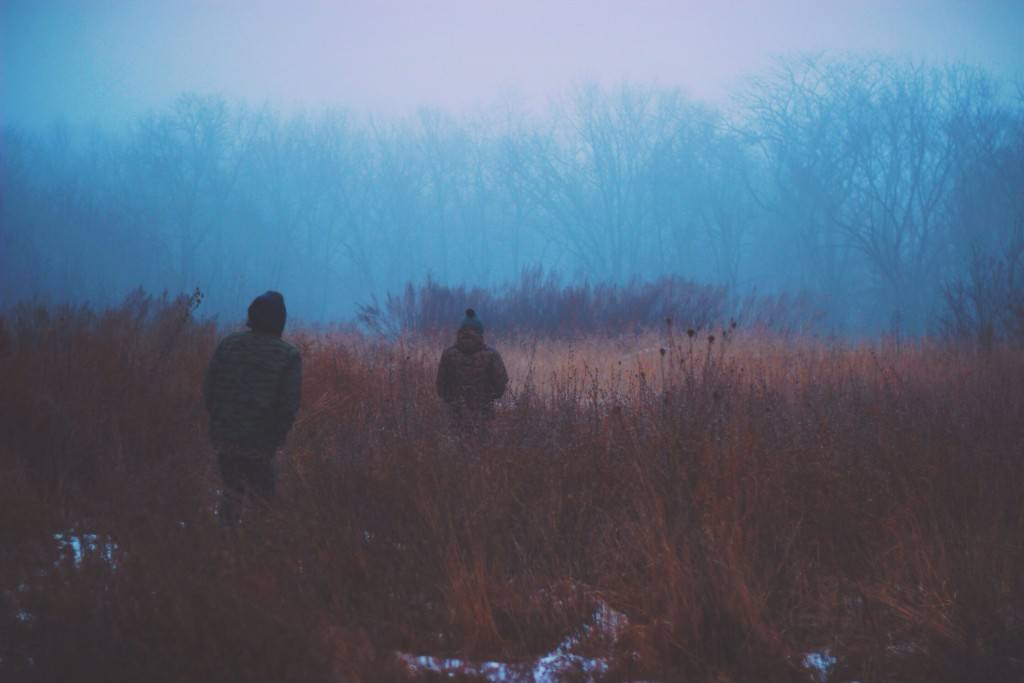 two people walk in tall scrub brush with patchy snow in the cold