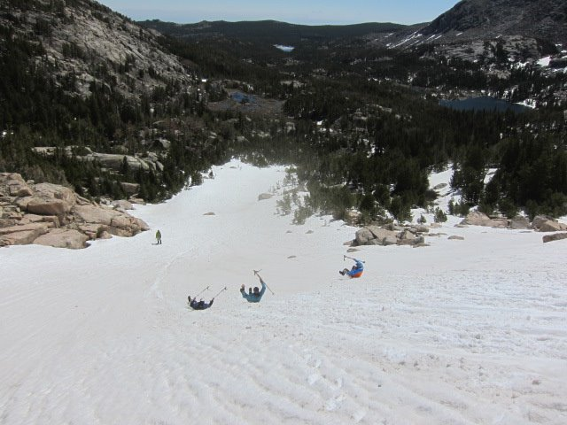 NOLS participants practice self-arrest with trekking poles on a snowy slope in the Wind River Range