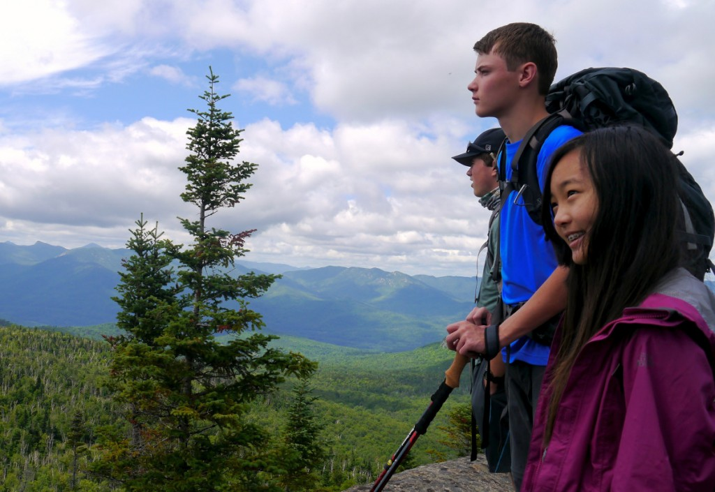 A group of teens overlooks a forested mountain valley