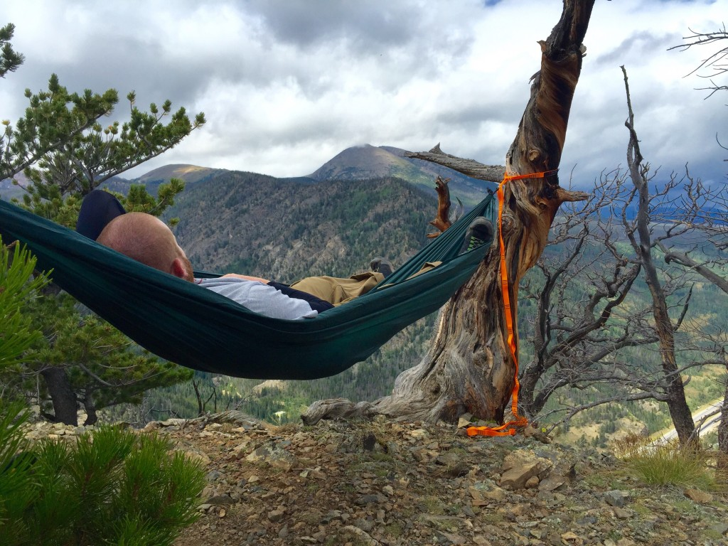 man naps in a green hammock overlooking forested mountains