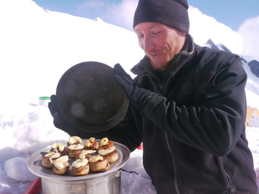 Man lifts the lid on a pan of cinnamon rolls in a snow kitchen