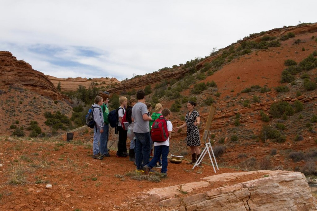woman teaches schoolchildren outdoors in a red rock canyon