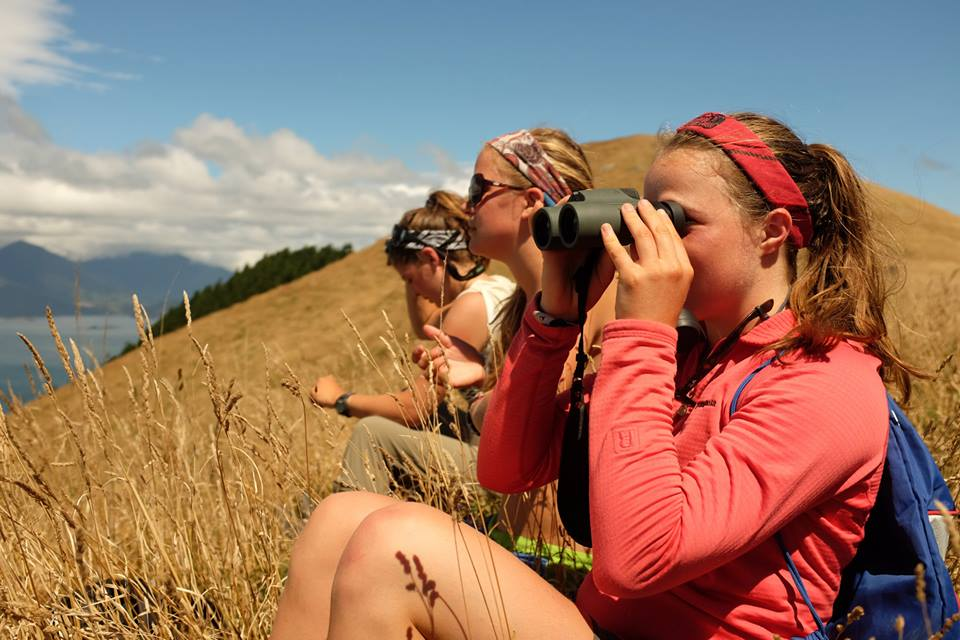 A group of NOLS students looks at the landscape through binoculars