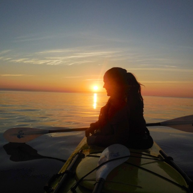 Silhouette of a sea kayaker at sunset