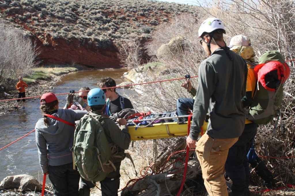 NOLS wilderness medicine students participate in a scenario by the river at the Wyss Campus in Lander
