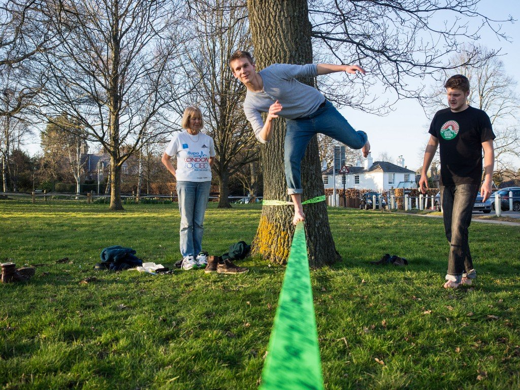 man balances on one foot on a slack line while two friends watch