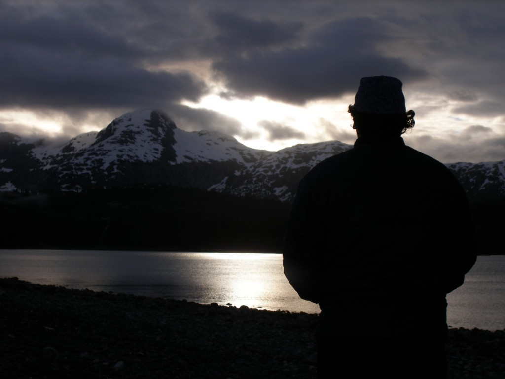silhouetted figure faces snow-covered mountains