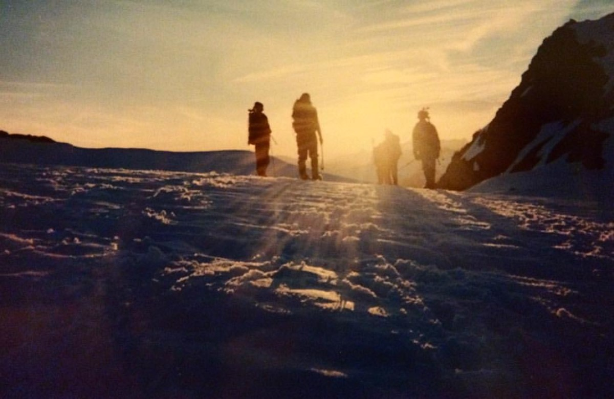 Four silhouetted figures on a snowfield in the mountains at sunset