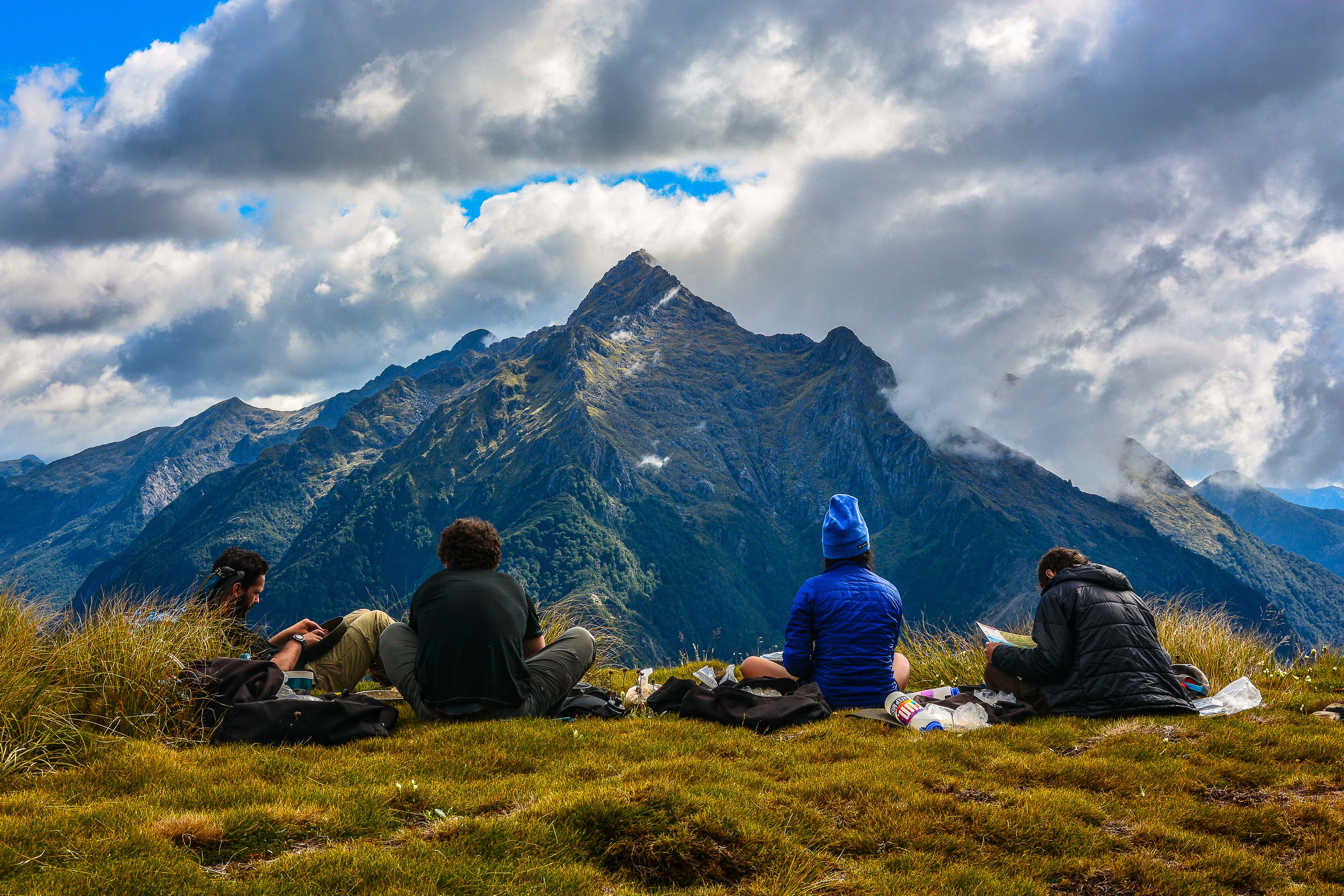 Four students preparing a meal while overlooking a New Zealand mountain range