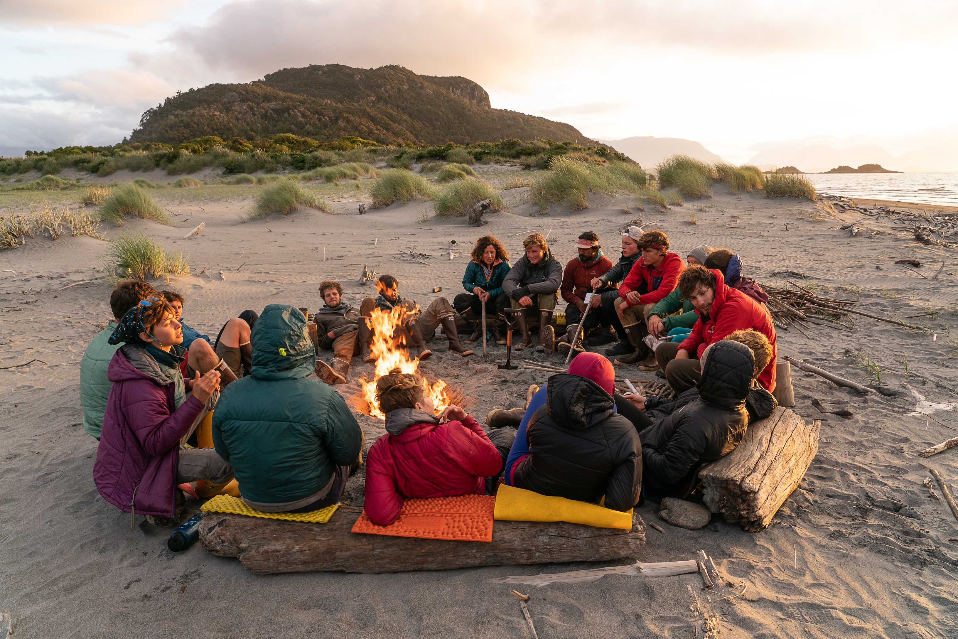 Group of students sitting in a circle around a fire on a beach in Patagonia at sunset