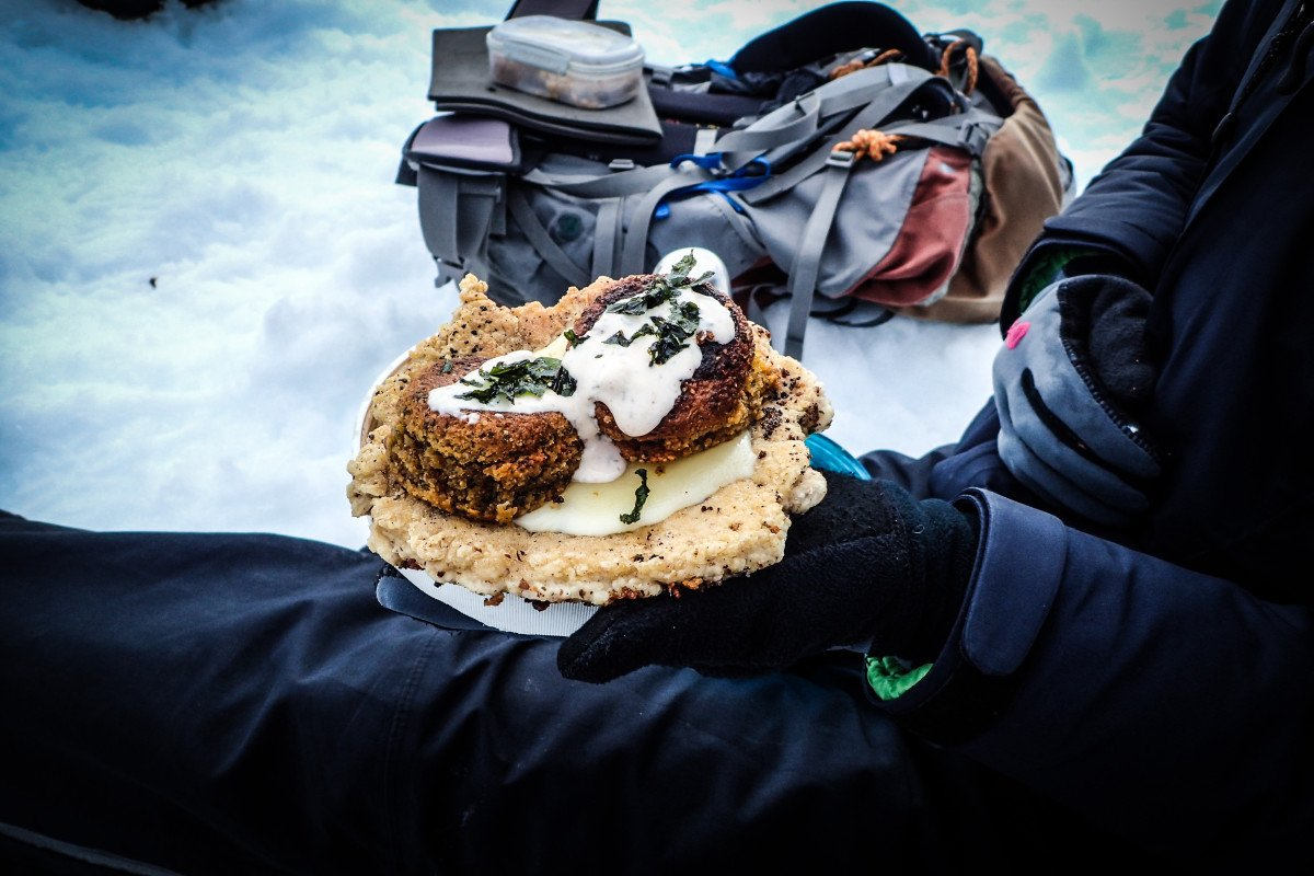 Person wearing gloves and winter gear sits in the snow holding a serving of backcountry falafel with a backpack nearby