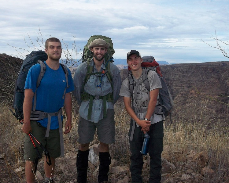 three NOLS students smile while backpacking