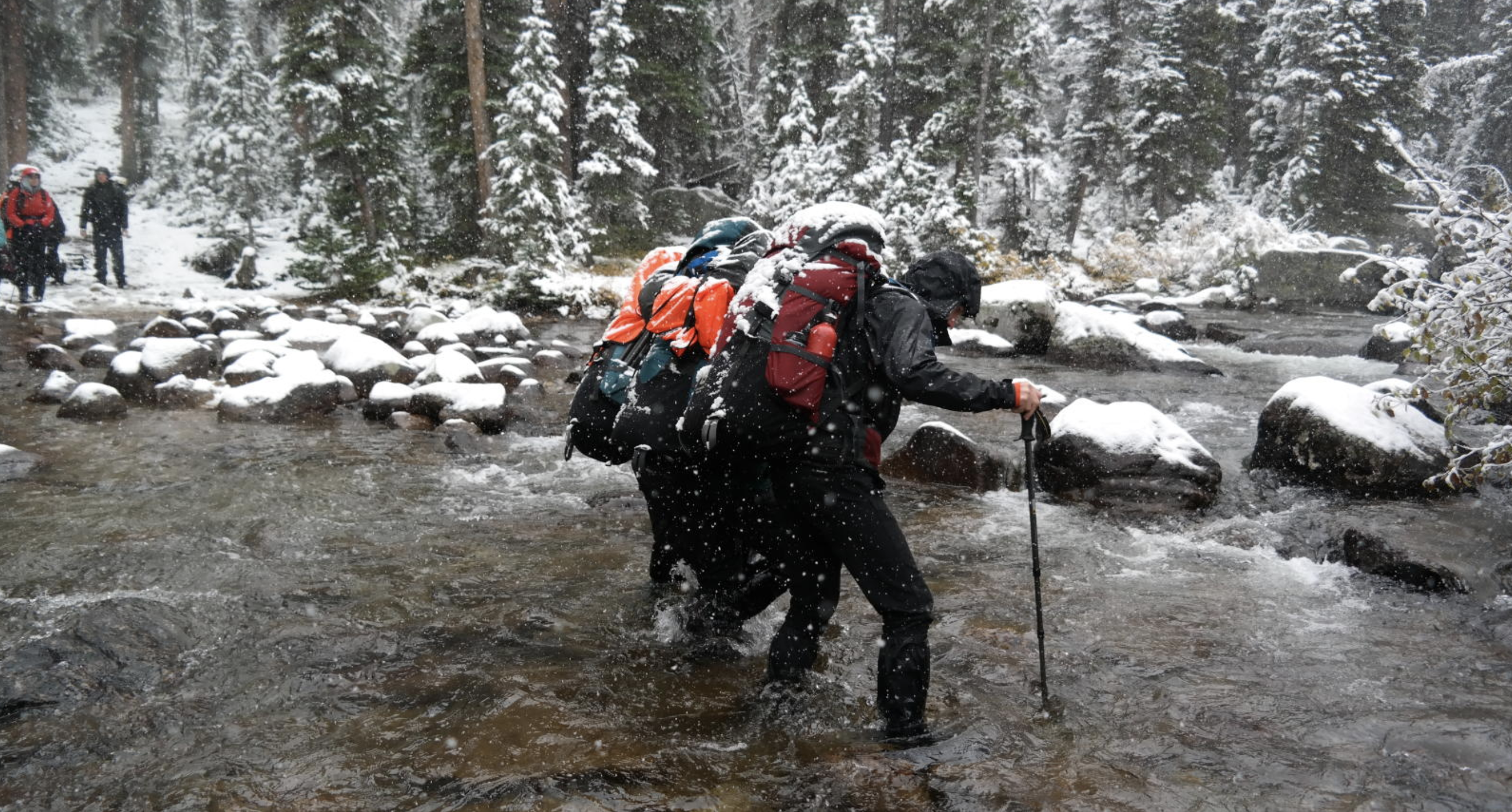 Two men with heavy backpacks cross a snowy river.