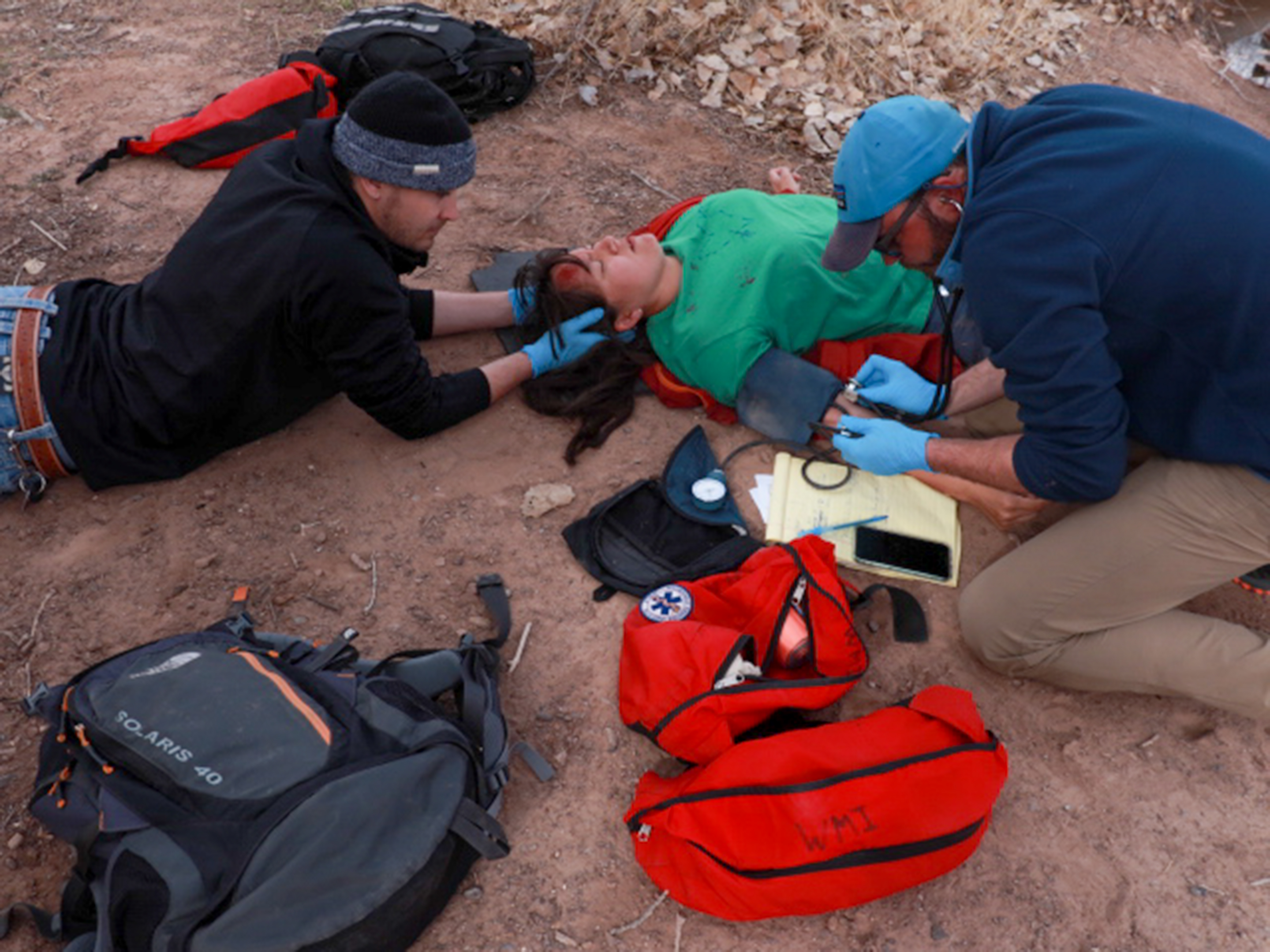 Two rescuers stabilize an unconscious patient's head and check her blood pressure.