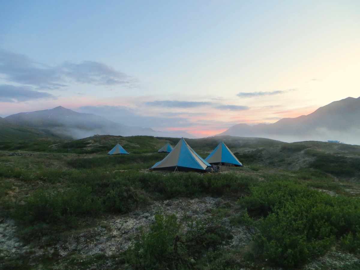 blue and tan mega mid tents pitched in Alaska at sunset