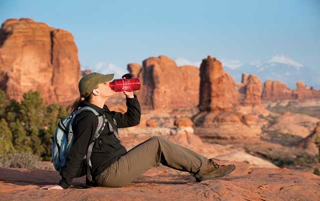 hiker sits down to drink water from a red bottle in a landscape of red rock