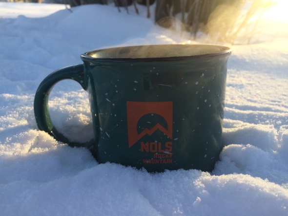 Green coffee mug steaming in the snow