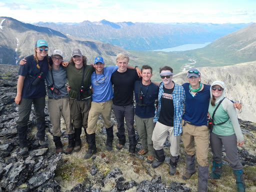 Nine smiling NOLS students stand in a line with arms around each other in Alaska's mountains