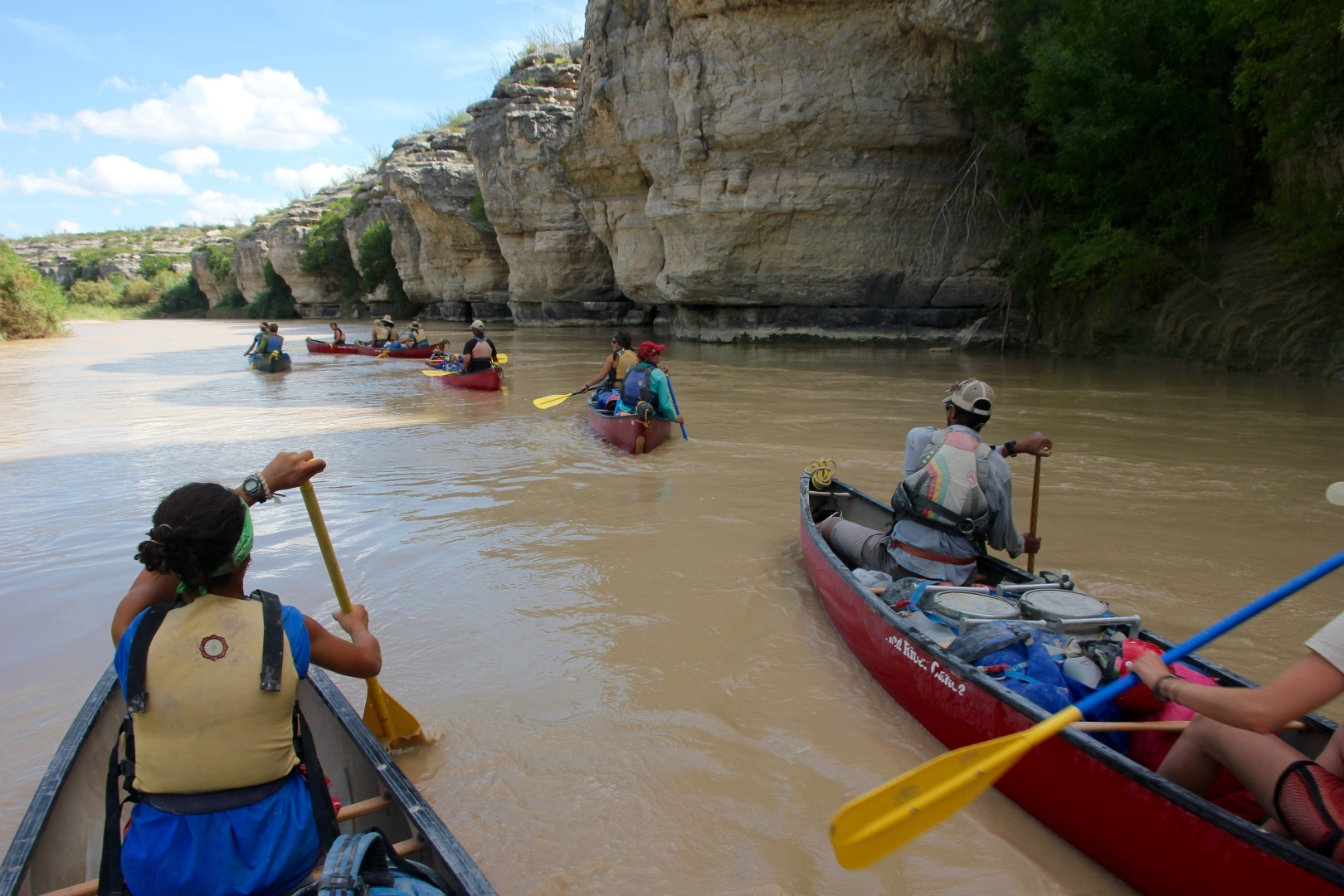 A large group of people canoeing on a river with canyon walls on the right