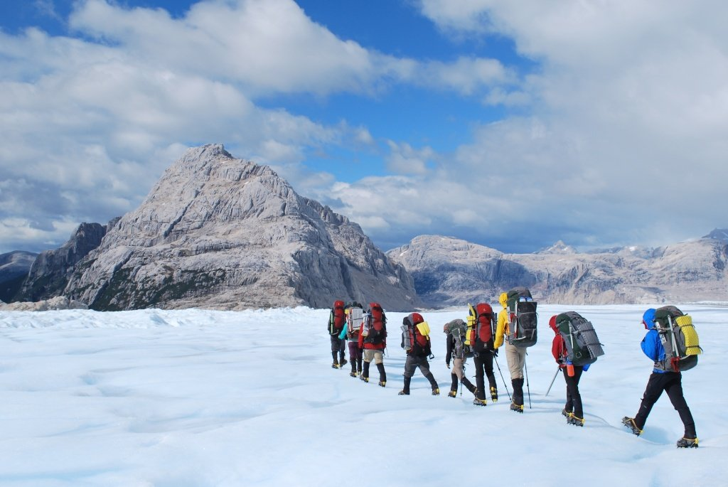 line of NOLS students hike across a snowfield toward rocky peaks using trekking poles