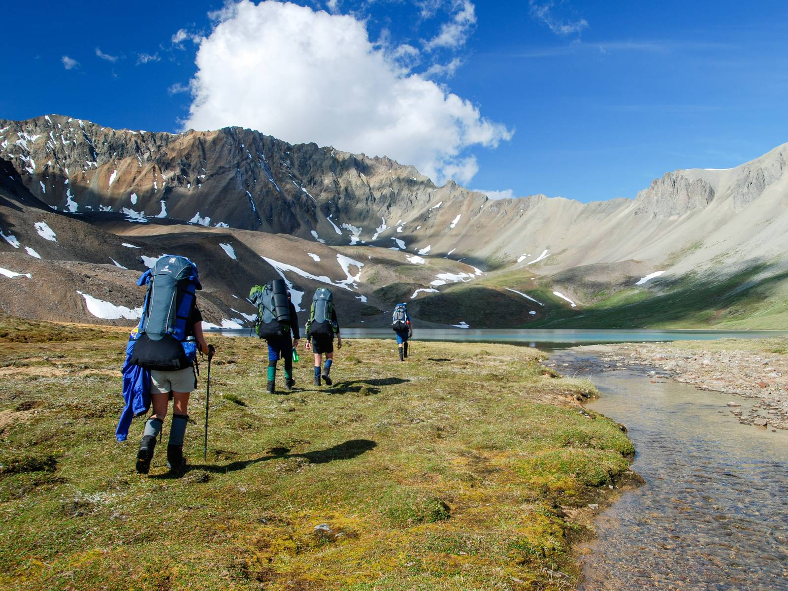 Group hiking across a green valley toward an alpine lake on a sunny day in Alaska