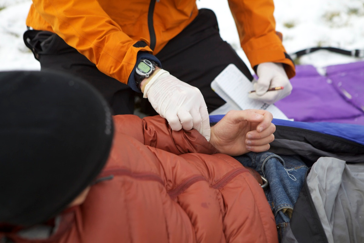 Person wearing orange jacket and white rubber gloves practices taking vitals on a patient lying in the snow