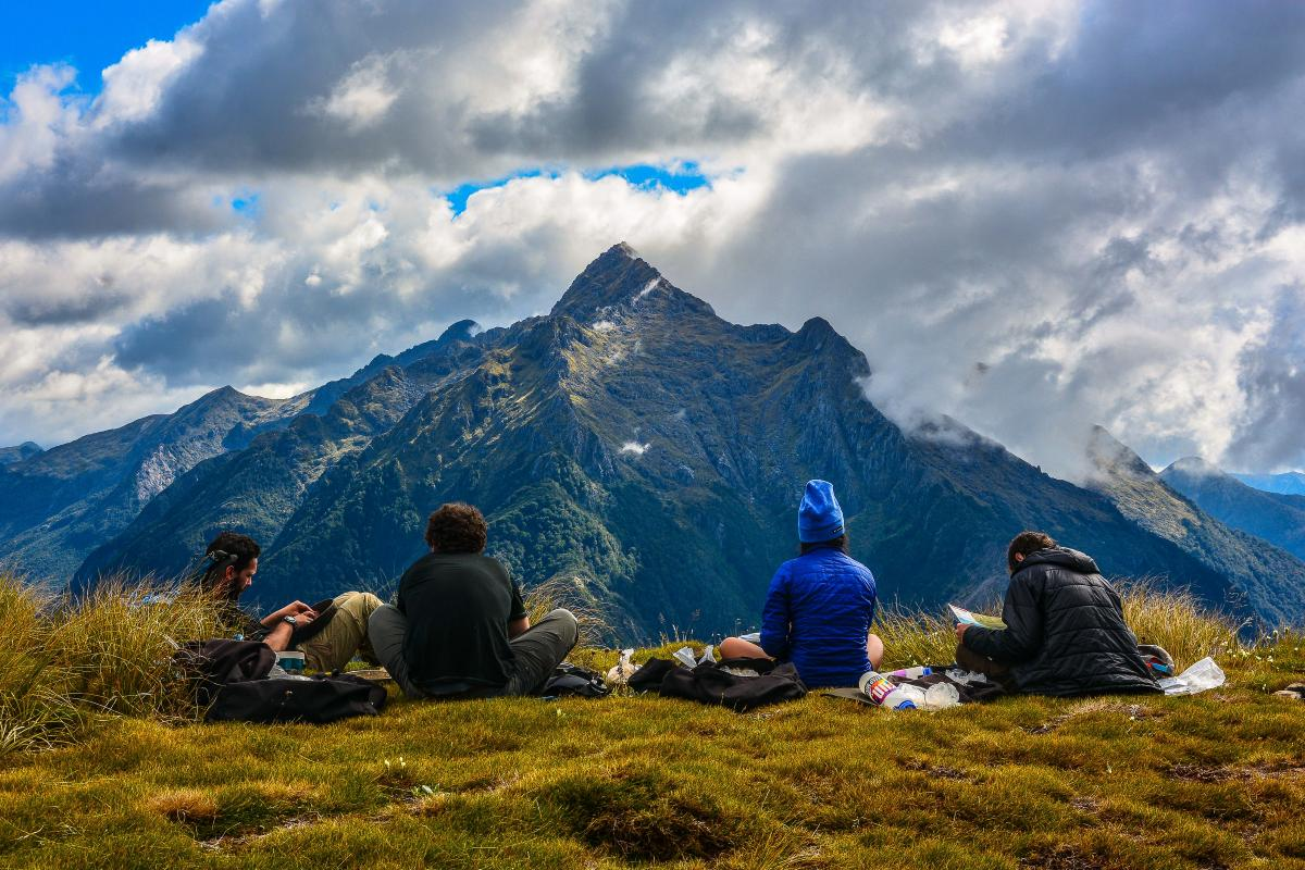 NOLS students sit on the grass and rest, gazing out at rugged peaks with clouds overhead in New Zealand